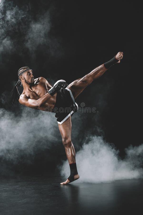 Ideia lateral do pontapé praticando tailandês muay concentrado do lutador no preto imagens de stock royalty free