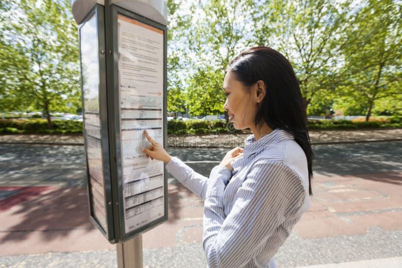 Ideia lateral do sinal asiático novo da informação da leitura da mulher de negócios na rua imagens de stock