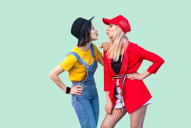 Ideia lateral dos pares de melhores amigos bonitos do moderno do stilysh na roupa elegante que está, levantando e enviando o beij fotos de stock royalty free