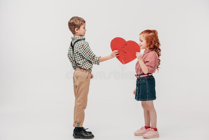 ideia lateral dos pares pequenos bonitos que guardam partes de coração quebrado fotos de stock royalty free