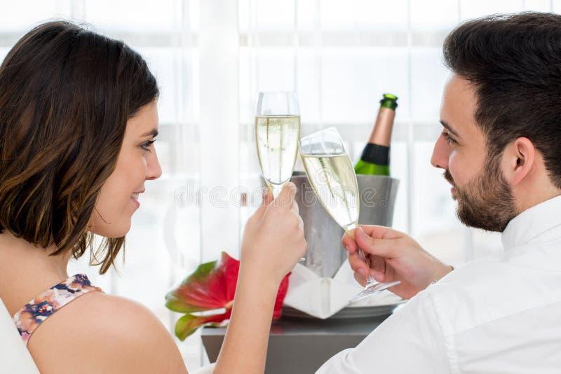 Ideia lateral dos pares que comemoram com vinho espumante fotografia de stock