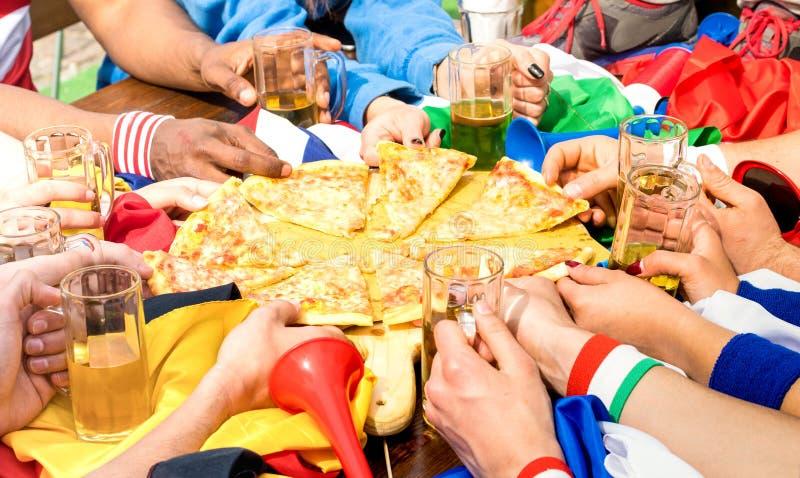 Ideia lateral superior das mãos multirraciais do suporte dos amigos do futebol que compartilha do margherita no restaurante - con fotografia de stock