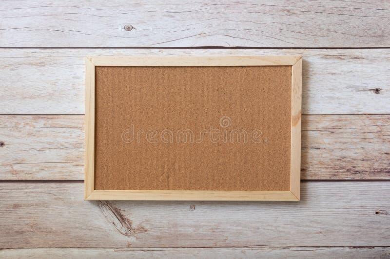 A ideia lisa da zombaria vazia da placa da cortiça decora acima com etiquetas na tabela de madeira Área lisa para o espaço da fot imagens de stock