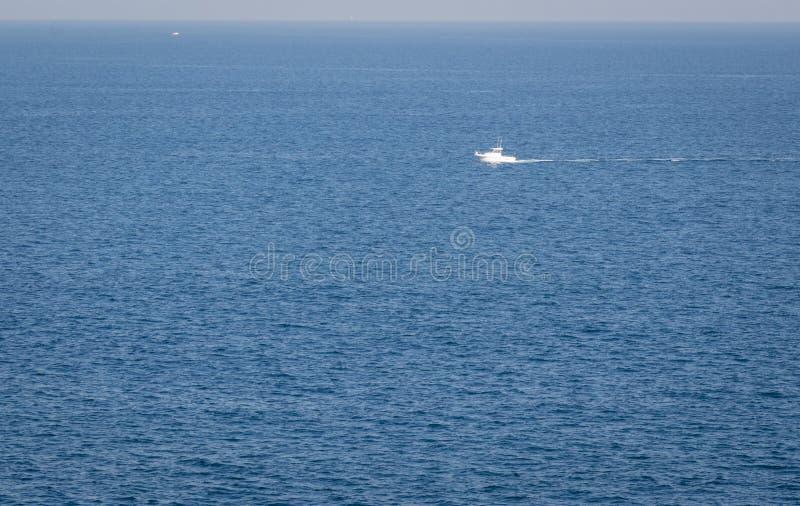 Ideia mínima do seascape cantábrico da manhã do mar com um barco só que flutua no meio do mar imagem de stock