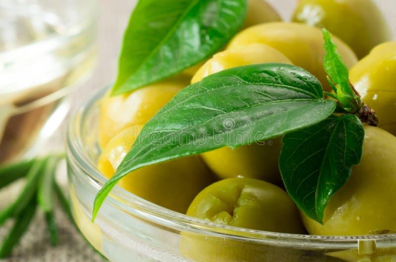 A ideia macro das azeitonas com verde deixa o close-up fotografia de stock