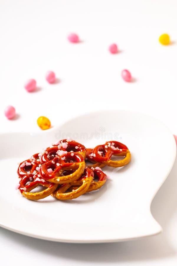 A ideia para o Valentim trata o chocolate do mergulho do pretzel na placa cerâmica da forma do coração no fundo branco com o espa fotos de stock royalty free