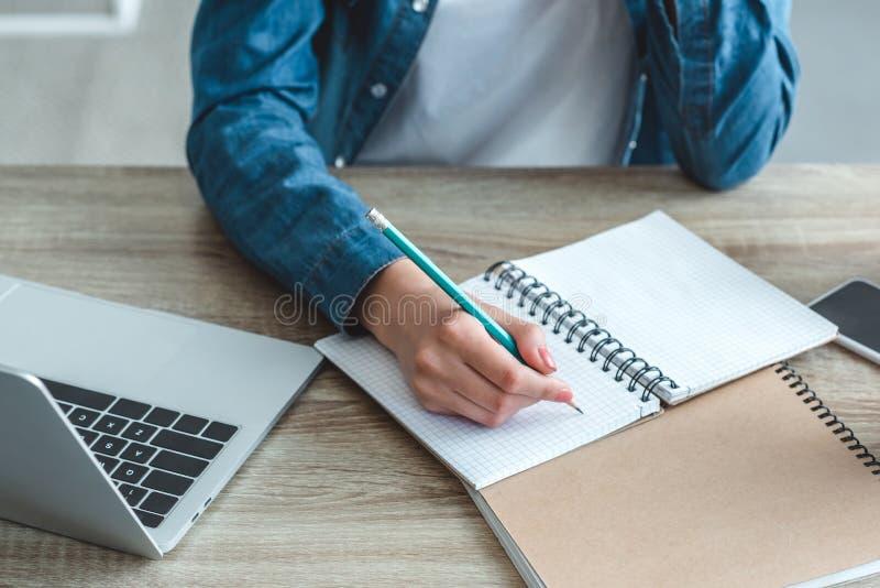 ideia parcial do close-up da escrita da menina no caderno ao estudar com portátil imagens de stock