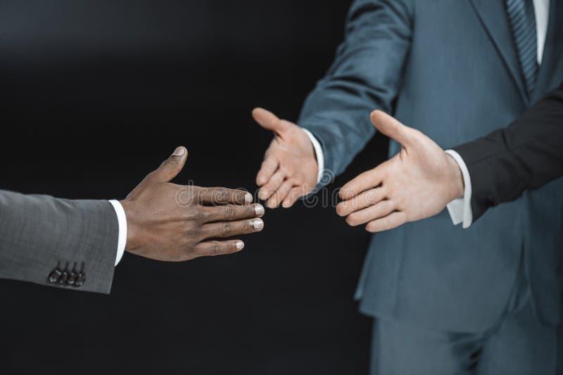 ideia parcial do grupo multi-étnico de homens de negócios que outstretching as mãos para o aperto de mão fotos de stock royalty free