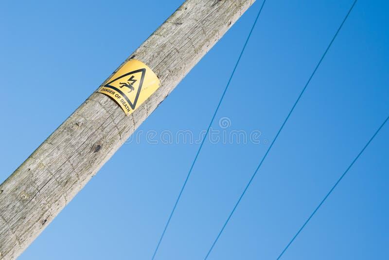 Ideia próxima do sinal do perigo no pólo da eletricidade fotos de stock royalty free