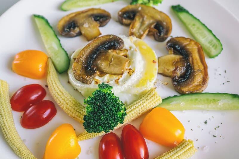 Ideia saudável da refeição matinal em ovos mexidos de uma placa do branco com os pepinos dos cogumelos do milho dos vegetais imagens de stock royalty free