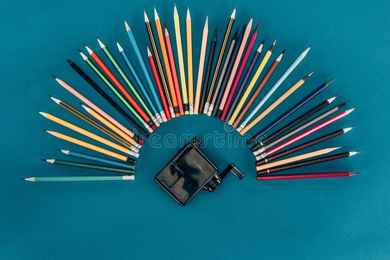 Ideia superior da composição de lápis e do apontador coloridos fotografia de stock royalty free