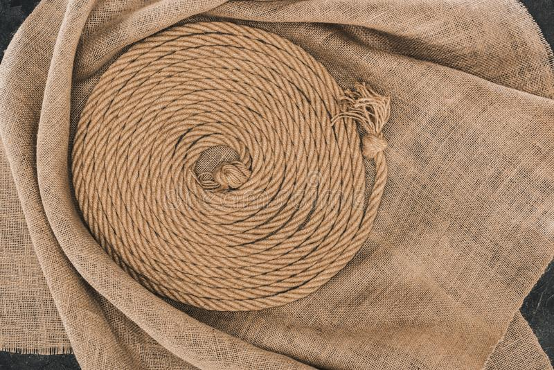 a ideia superior da corda náutica marrom arranjou no círculo no pano de saco na obscuridade fotos de stock royalty free