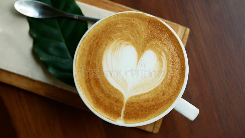 Ideia superior da forma quente do coração da arte do latte do cappuccino do café no copo cerâmico no fundo de madeira da tabela imagem de stock royalty free