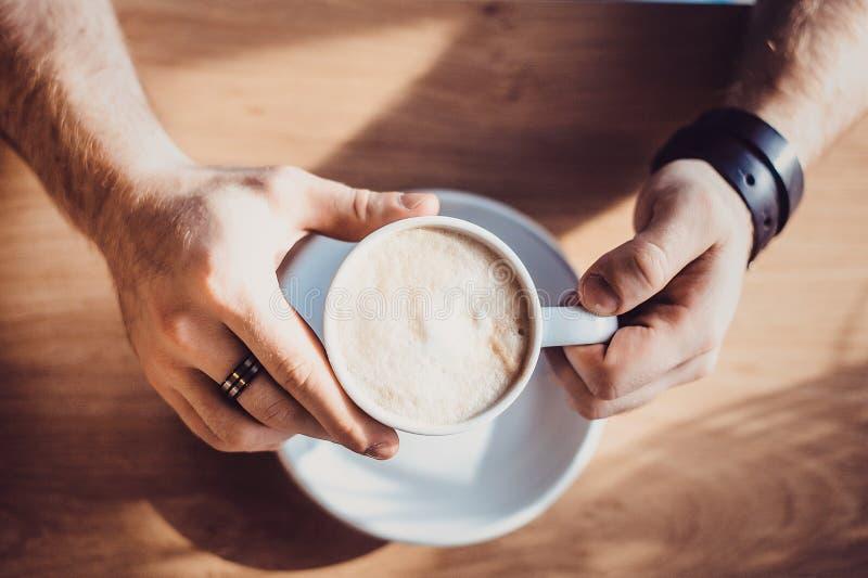 Ideia superior da mão do homem que guarda uma xícara de café, a xícara de café de A e a mão de um homem foto de stock