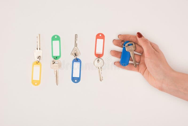 ideia superior da mão que guarda chave ao lado do grupo de chaves com etiquetas coloridas foto de stock royalty free
