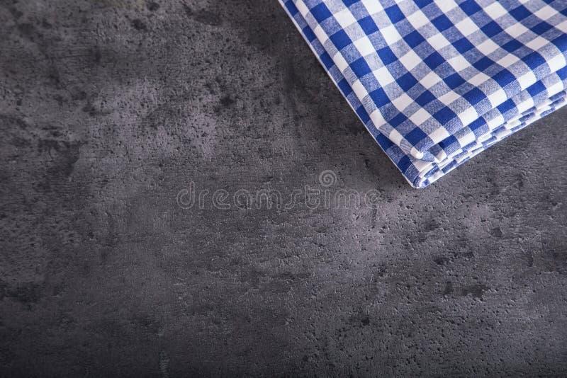 Ideia superior da toalha de mesa quadriculado da cozinha no granito - concreto - fundo de pedra Espaço livre para seus texto ou p imagem de stock royalty free