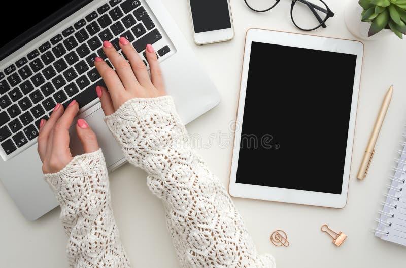 Ideia superior das mãos da mulher que datilografam no teclado numérico do portátil colocado no desktop branco do escritório com s foto de stock
