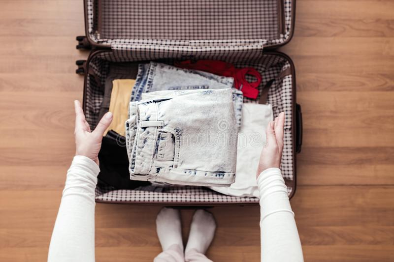 Ideia superior das mãos da mulher que embalam uma bagagem para uma viagem nova imagens de stock