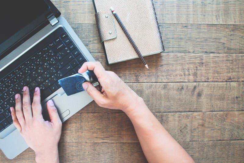 Ideia superior das mãos do homem que guardam o cartão de crédito e que usam o telefone esperto na tabela de madeira Conceito em l imagem de stock