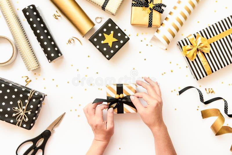 Ideia superior das mãos fêmeas que envolvem caixas de presente, materiais de envolvimento dispersados em vários projetos pretos,  imagem de stock royalty free