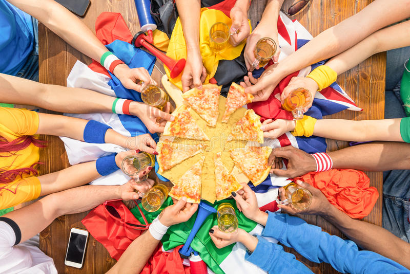 Ideia superior das mãos multi-étnicos do suporte do esporte que compartilham da pizza imagens de stock
