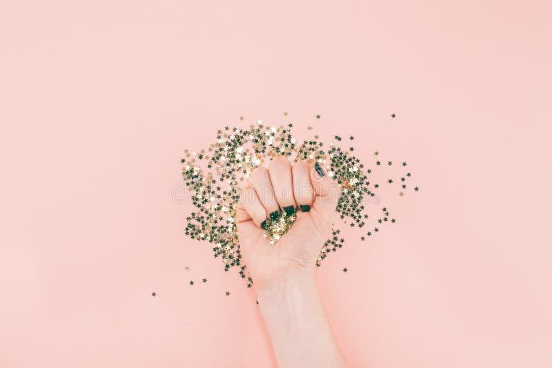 A ideia superior de ano novo ou de Natal do tratamento de mãos preto das mãos da mulher cobriu confetes dourados das estrelas com fotos de stock royalty free