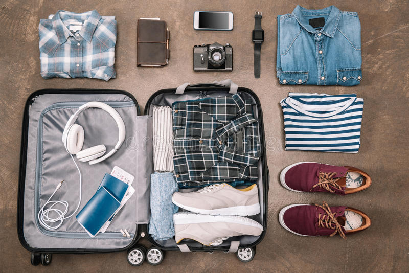 Ideia superior de artigos essenciais de umas férias na bagagem aberta com dispositivos digitais imagem de stock