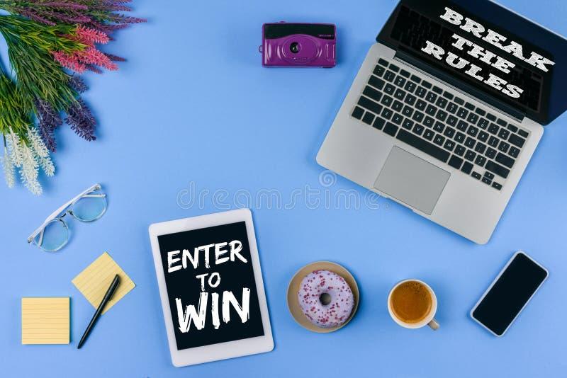 a ideia superior de dispositivos digitais com inscrição entra para ganhar e quebrar as regras, flores, xícara de café com filhós  ilustração stock