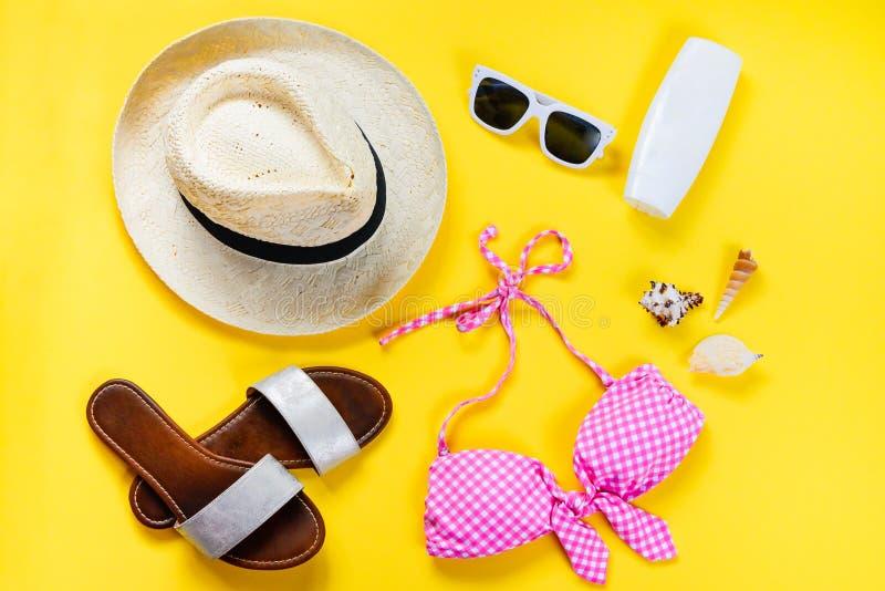 Ideia superior de duas accessoties cor-de-rosa partes do terno e da praia de natação sobre o fundo amarelo foto de stock royalty free