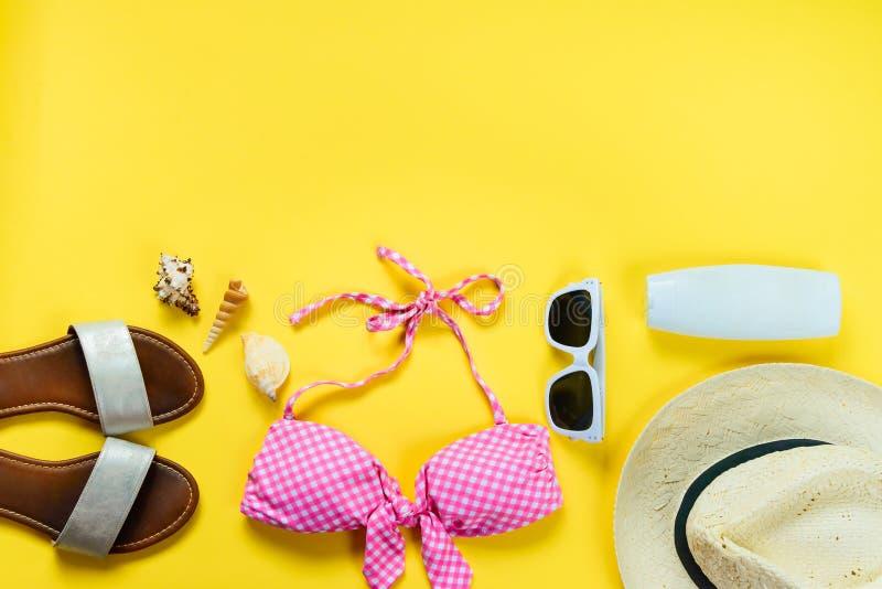 Ideia superior de duas accessoties cor-de-rosa partes do terno e da praia de natação sobre o fundo amarelo imagem de stock royalty free