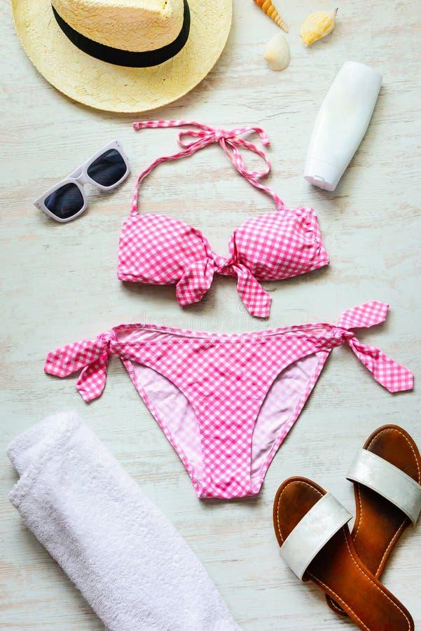 Ideia superior de duas accessoties cor-de-rosa partes do terno e da praia de natação sobre o fundo de madeira imagem de stock royalty free