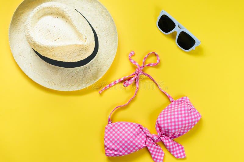 A ideia superior de duas partes do rosa chequered o terno de natação, os óculos de sol brancos e o chapéu de palha sobre o fundo  imagens de stock