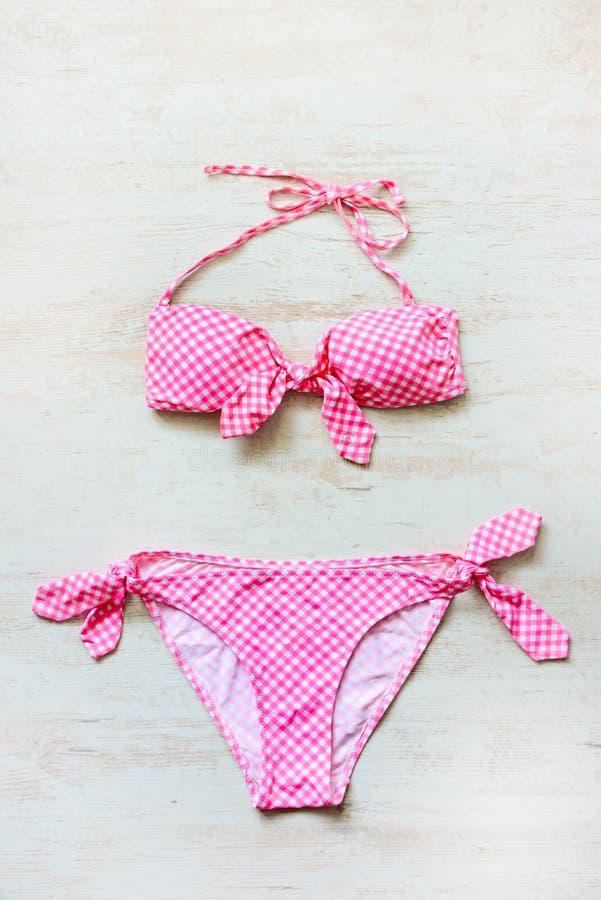 A ideia superior de duas partes do rosa chequered o terno de natação sobre o fundo de madeira foto de stock