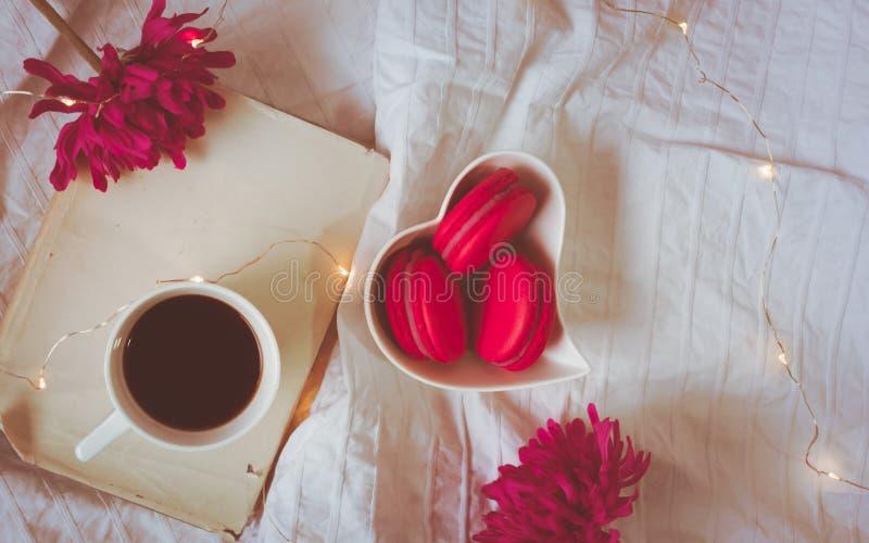 Ideia superior de macarons vermelhos ou cor-de-rosa em uma bacia, em um café, em um livro e em umas flores dados forma coração foto de stock royalty free