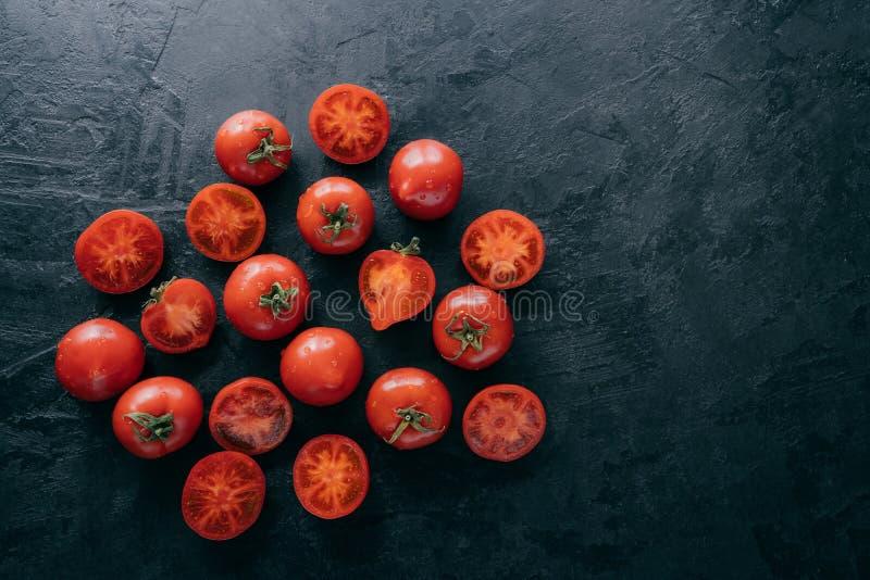 Ideia superior de tomates e de fatias muito maduros no fundo escuro com espaço livre Legumes frescos orgânicos que contêm vitamin fotos de stock