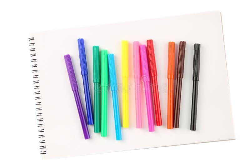 Ideia superior de um grupo de doze marcadores coloridos da ponta de feltro em um scetchbook vazio isolado no fundo branco imagem de stock royalty free