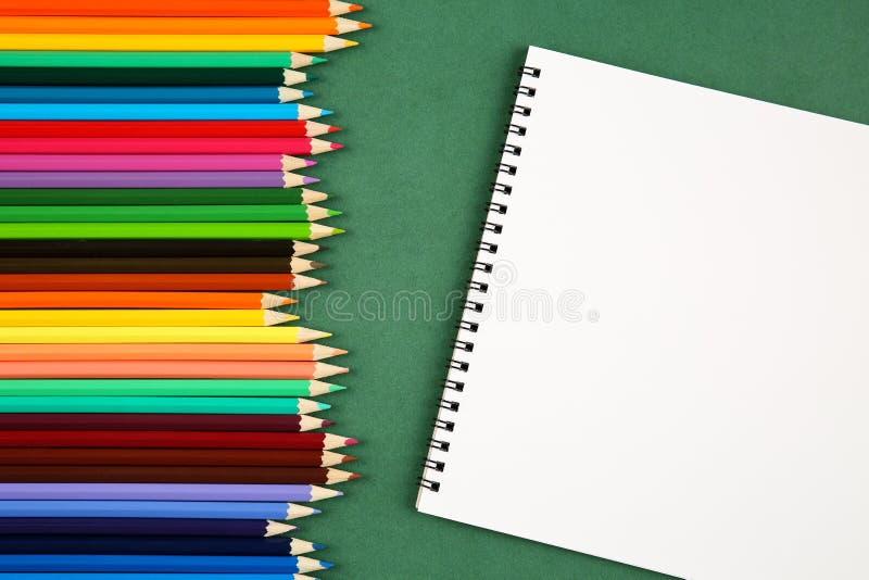 Ideia superior de um grupo de muitos lápis coloridos e bloco de desenho vazio com um espaço da cópia em um fundo verde Arte, ofíc foto de stock royalty free
