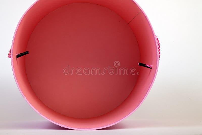 Ideia superior de um interior vazio redondo da caixa de cartão do rosa cor-de-rosa para o papel de embrulho em um close-up branco foto de stock