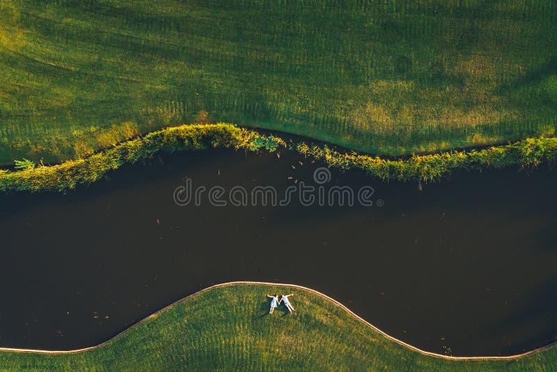 Ideia superior de um par que coloca na grama perto do rio fotos de stock royalty free