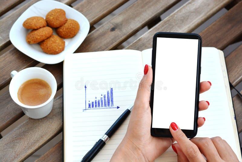 Ideia superior de um smartphone ou de um telefone celular com a tela vazia branca contra a tabela de trabalho fotos de stock royalty free