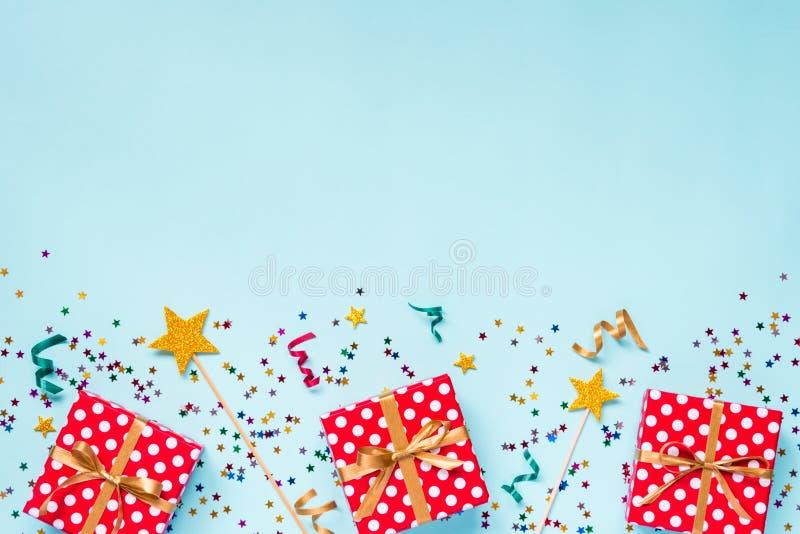 A ideia superior de um vermelho pontilhou caixas de presente, varinhas mágicas douradas, confetes coloridos e fitas sobre o fundo imagem de stock royalty free