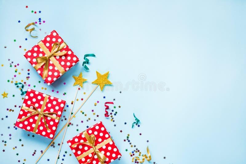 A ideia superior de um vermelho pontilhou caixas de presente, varinhas mágicas douradas, confetes coloridos e fitas sobre o fundo foto de stock
