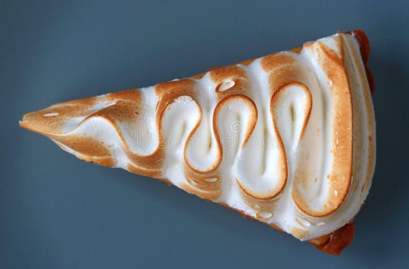 Ideia superior de uma fatia de galdéria da merengue do limão na placa azul fotografia de stock