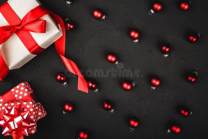 A ideia superior superior de uma fita, de um presente, e de um lote vermelhos da árvore brinca em um fundo preto de pedra foto de stock royalty free