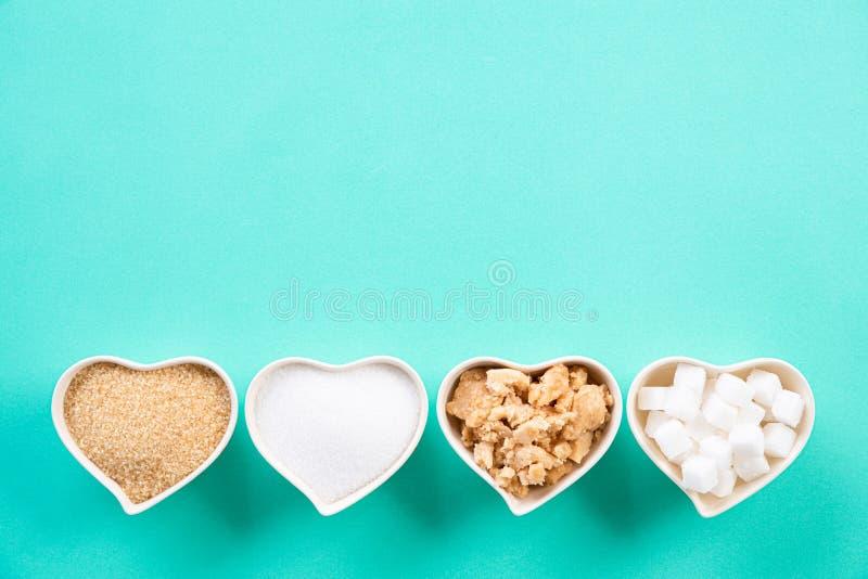 Ideia superior de vários tipos de açúcar Açúcar de cubo, açúcar mascavado do açúcar cru e açúcar granulado na bacia do coração na fotografia de stock