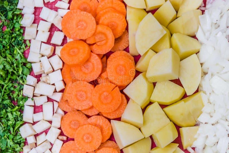 A ideia superior de vários vegatables cutted nas partes pequenas preparadas para o cozimento da sopa do vegetariano foto de stock