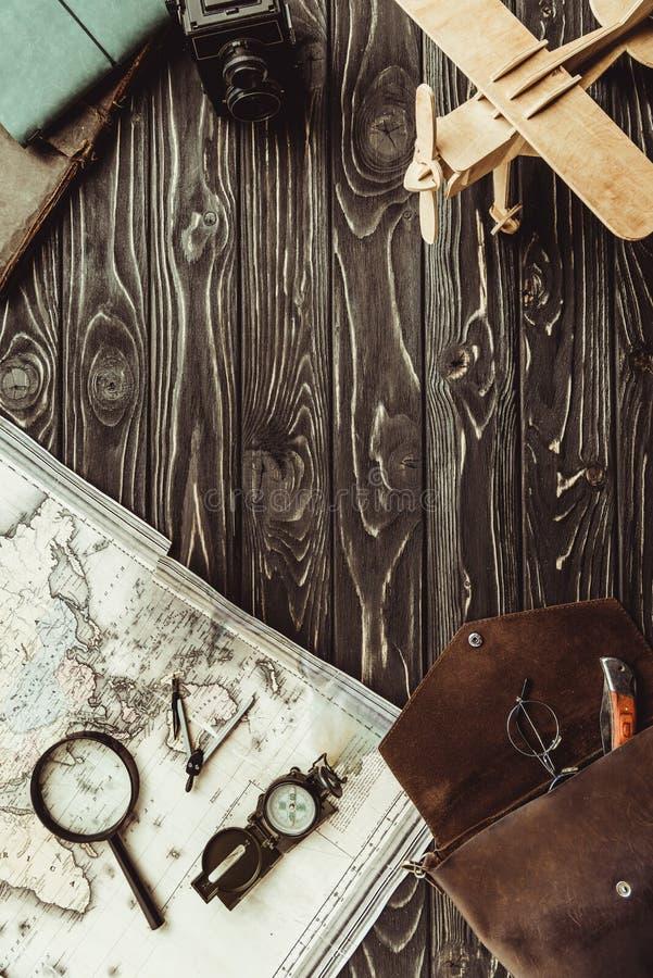 ideia superior do arranjo com mapa, lupa, saco, plano de madeira do brinquedo e a câmera retro da foto na obscuridade imagem de stock royalty free