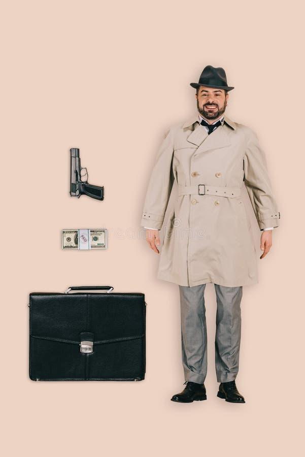 ideia superior do assassino masculino no chapéu com dinheiro e pasta do revólver foto de stock