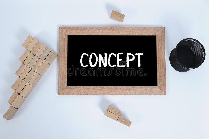 Ideia superior do CONCEITO escrita ? m?o com giz branco em um quadro-negro Copo do l?pis e bloco de madeira que empilham como o s imagens de stock