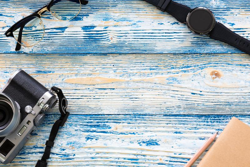 Ideia superior do conceito masculino do curso mínimo com vidros, relógio, câmera, caderno e lápis no claro - textura de madeira a imagem de stock